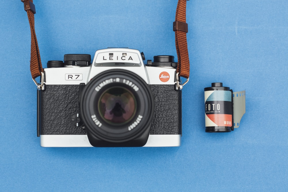 black and grey Leica camera on blue surface with film on side