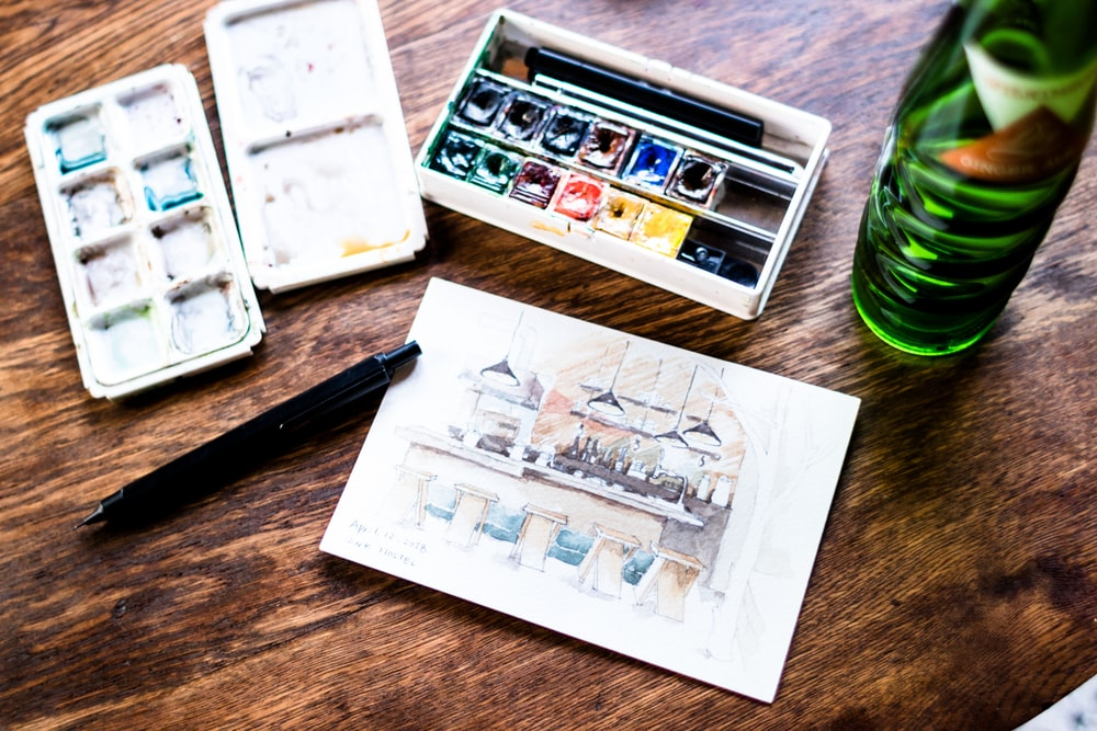 water color beside sketch paper on table