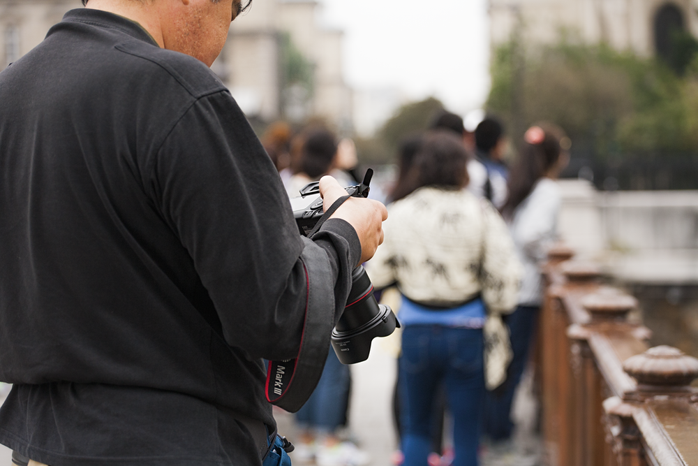 man checking his DSLR camera