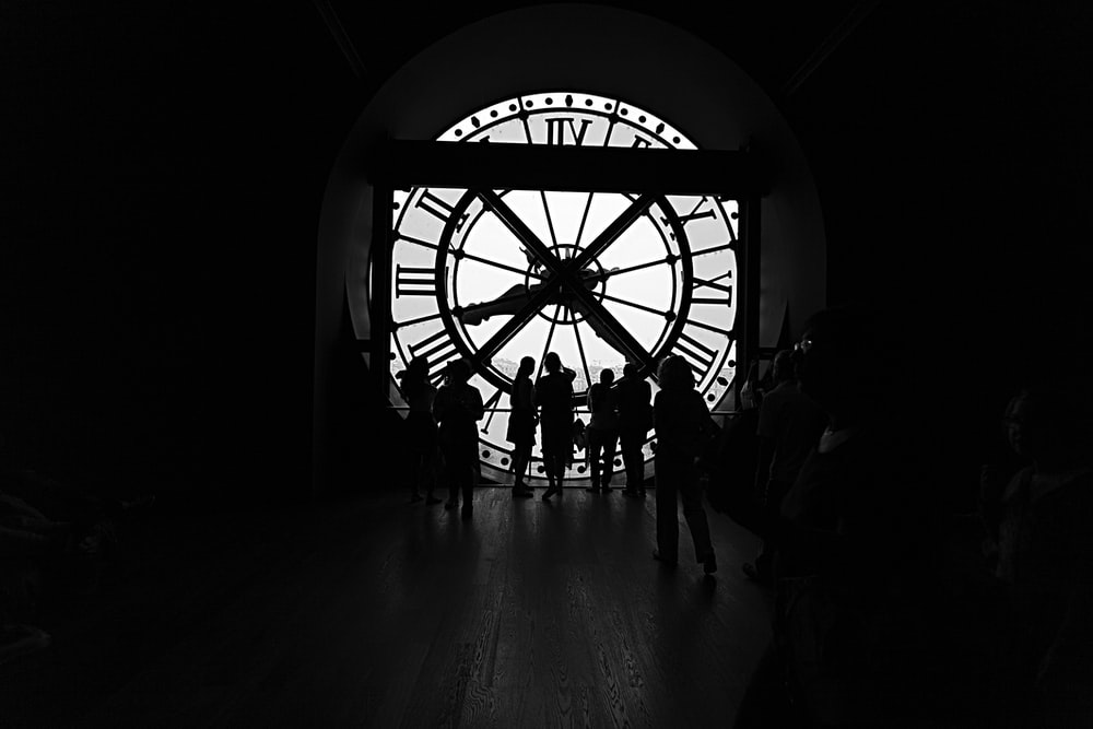 silhouette of people across large clock