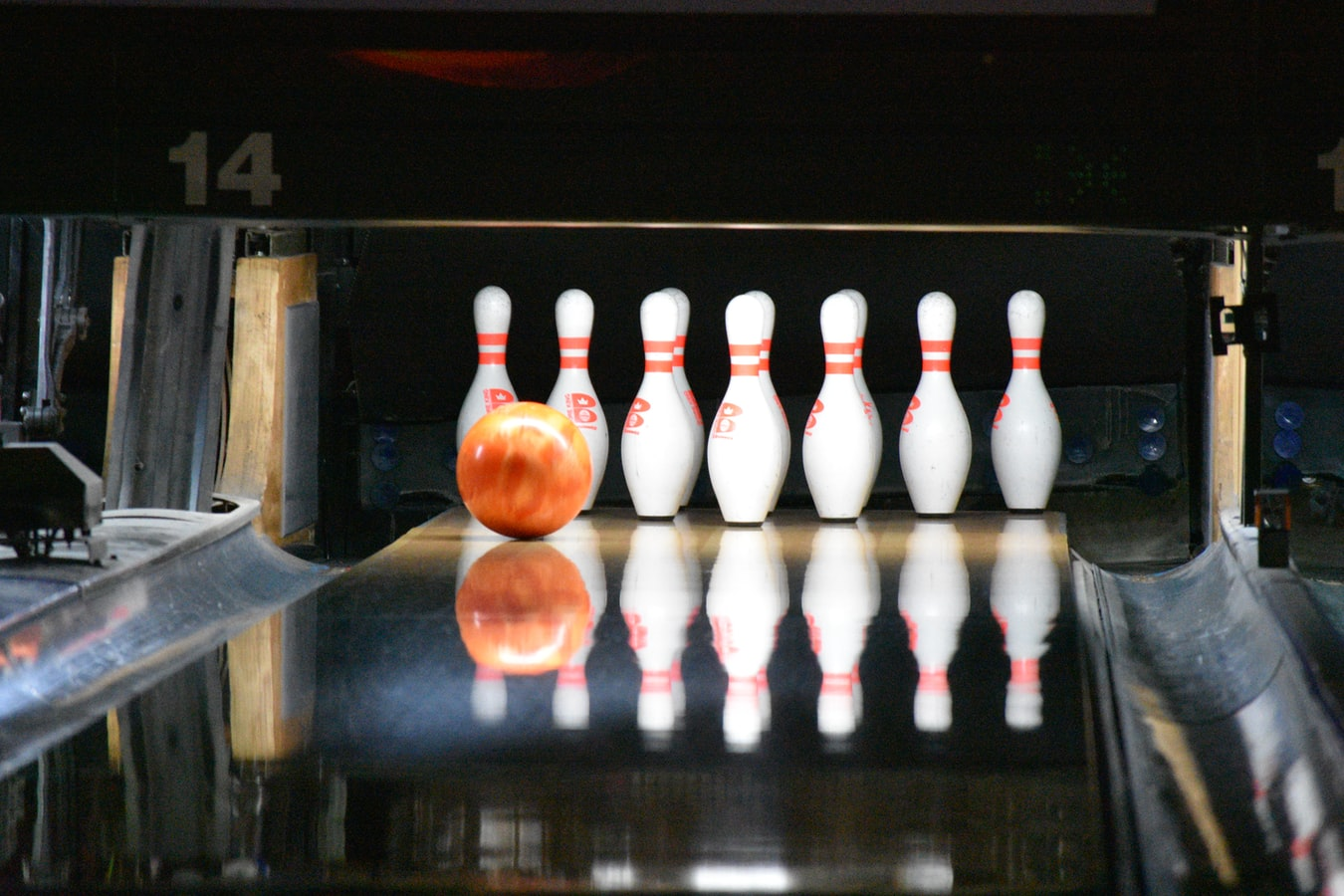 Orange bowling ball about to connect with pins at bowling alley