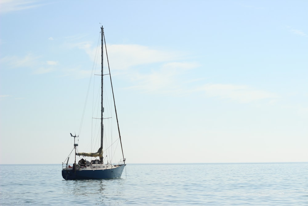 blue and white sail boat on body of water during daytime