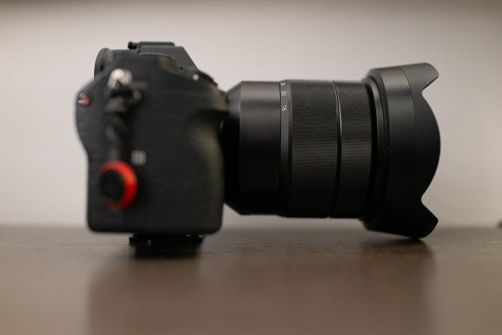 black SLR camera on brown wooden surface