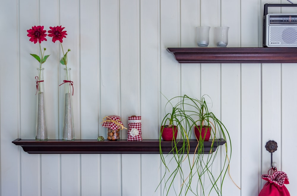 four vases on brown wooden floating shelf