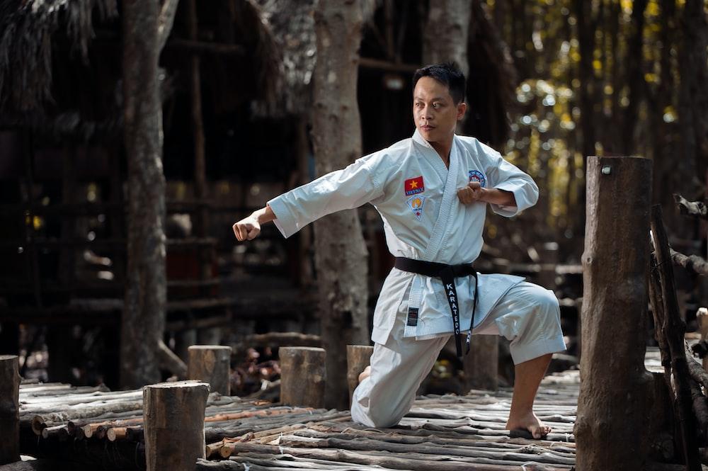 person wearing black belt karate gi training on wooden bridge