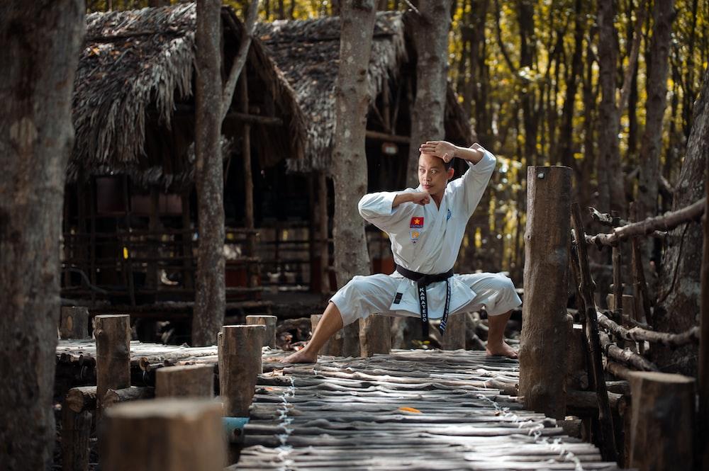 man wearing karate gi squatting on wooden dock