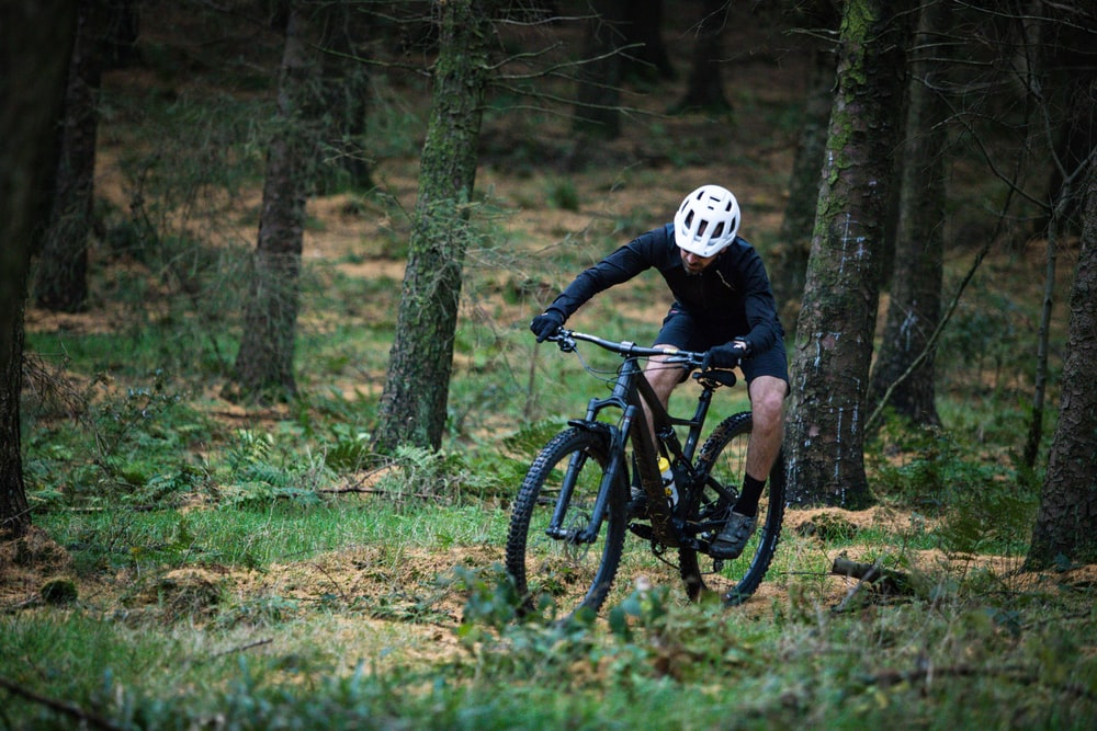 man riding on bike in the forest