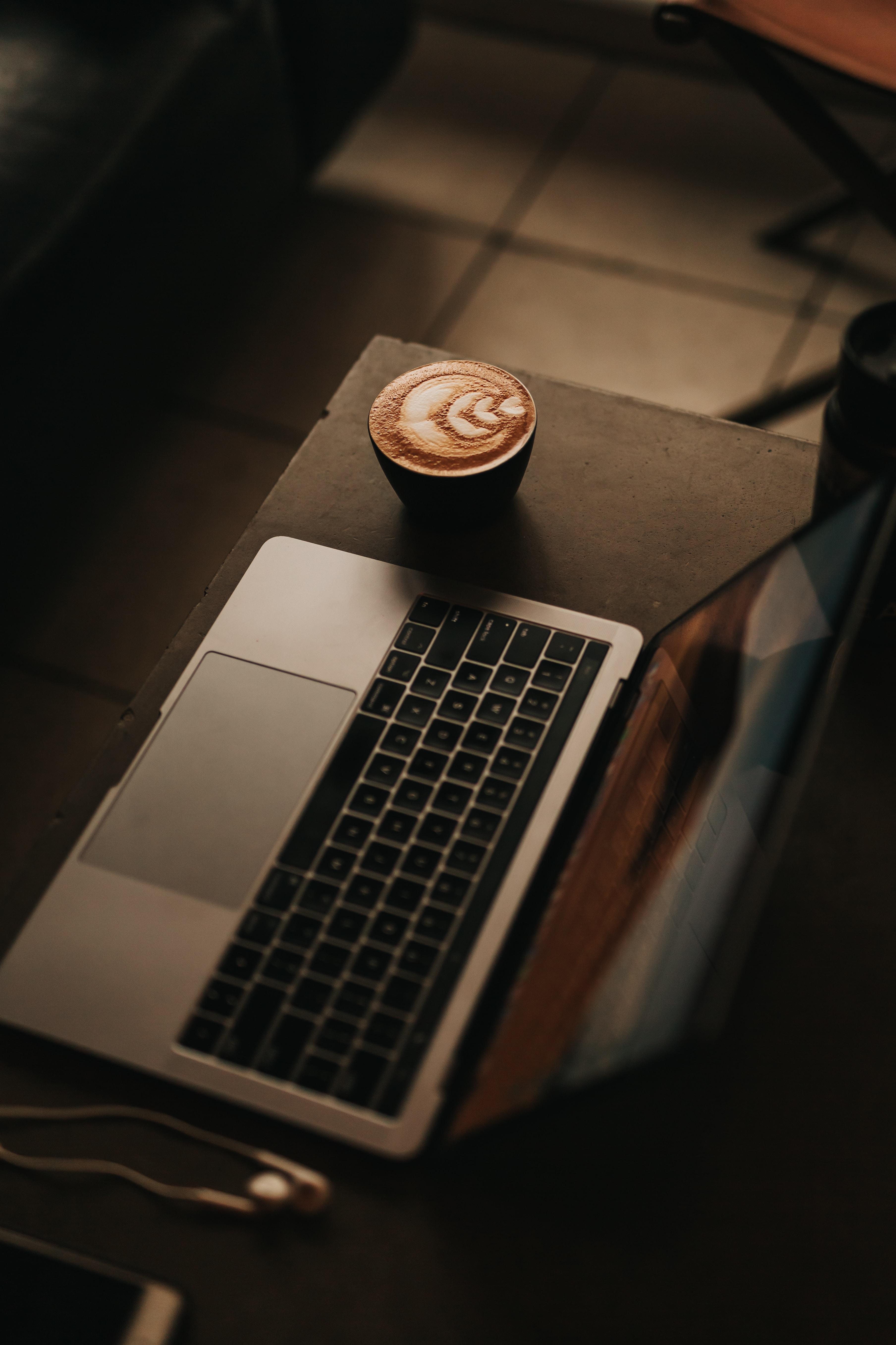 coffee latte beside MacBook Pro
