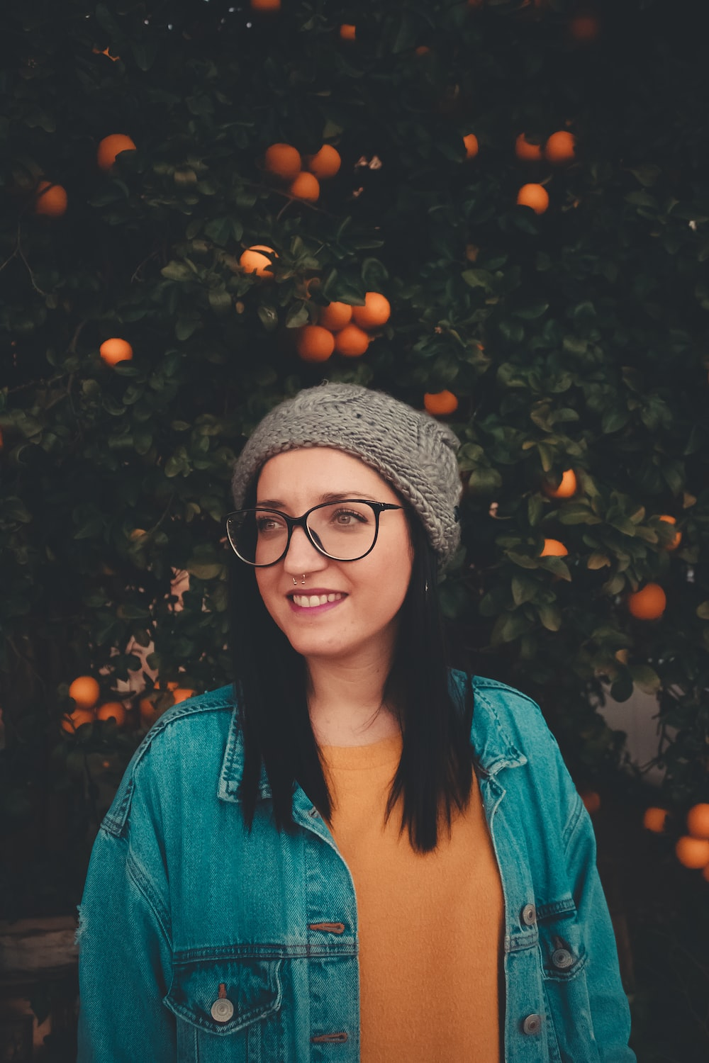 woman wearing blue denim jacket and grey beanie while standing near orange plant
