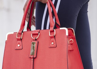 person carrying red leather handbag