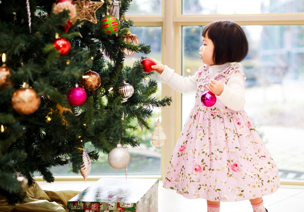 girl holding baubles near the Christmas