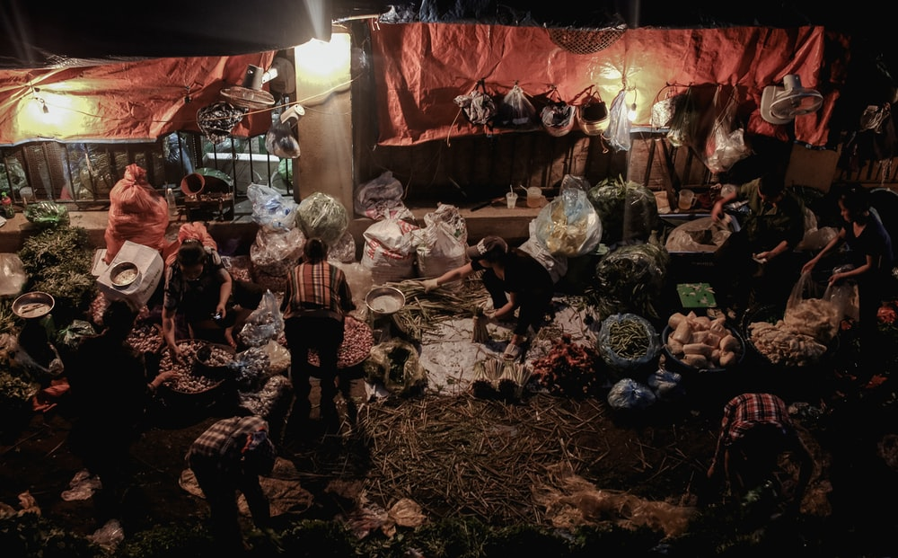 people standing near sacks during night time