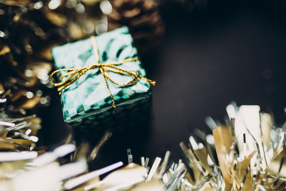 close up photography of green gift box decor near garlands