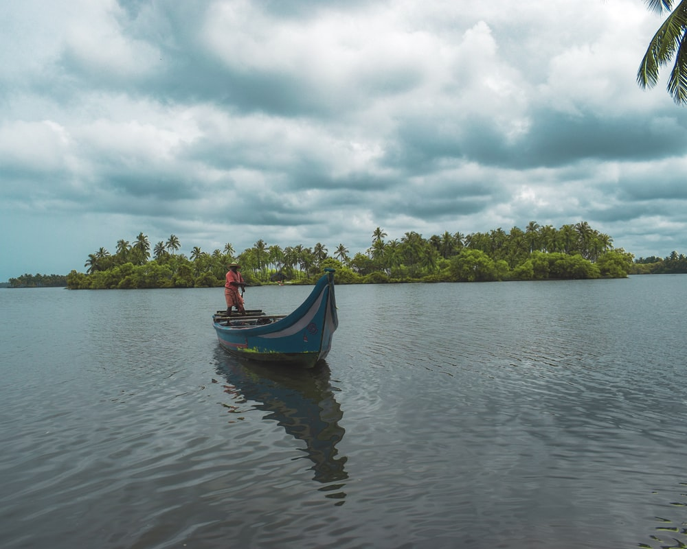 man standing on blue boat during cloudy day
