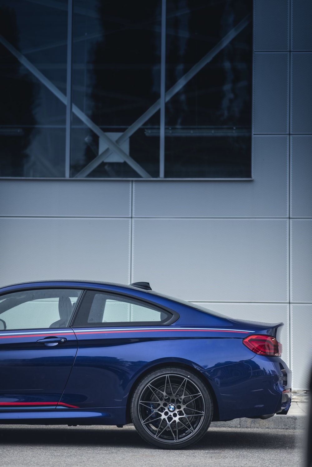 blue coupe parked near wall