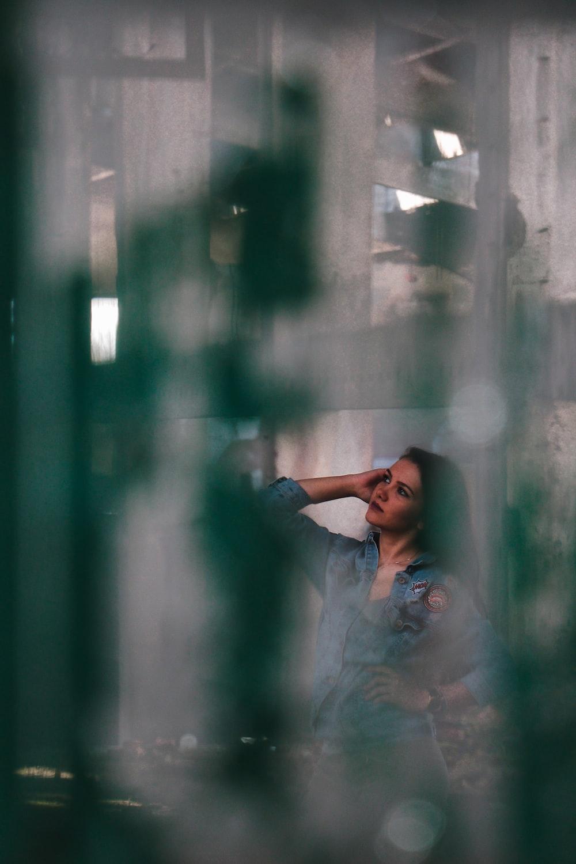 woman in blue dress sitting beside wall