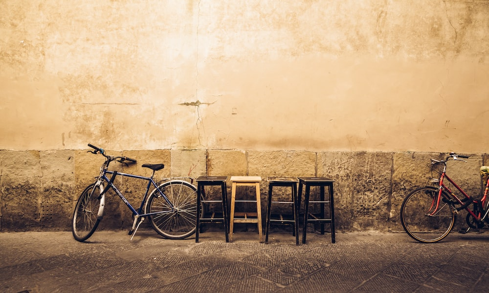 four bar stools near two bikes leaning on wall