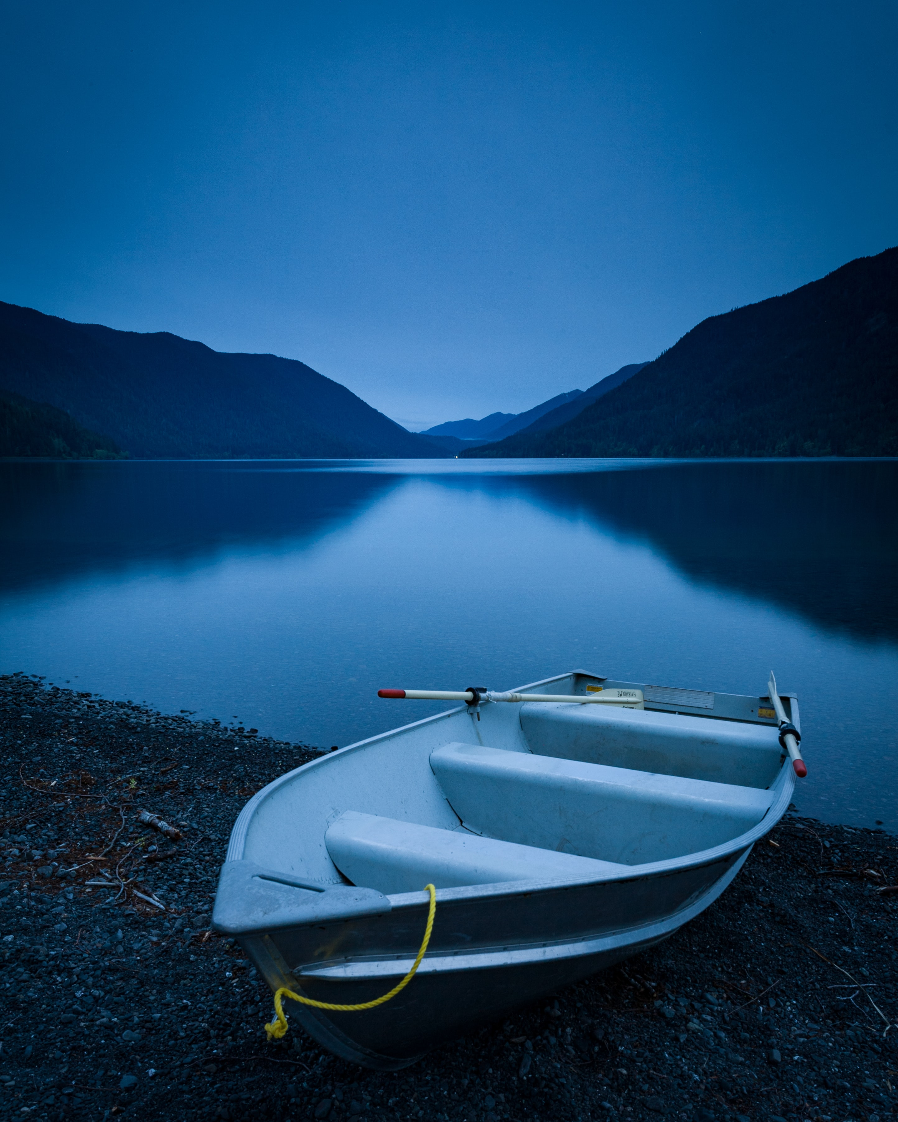 white rowboat near lake during clear blue sky