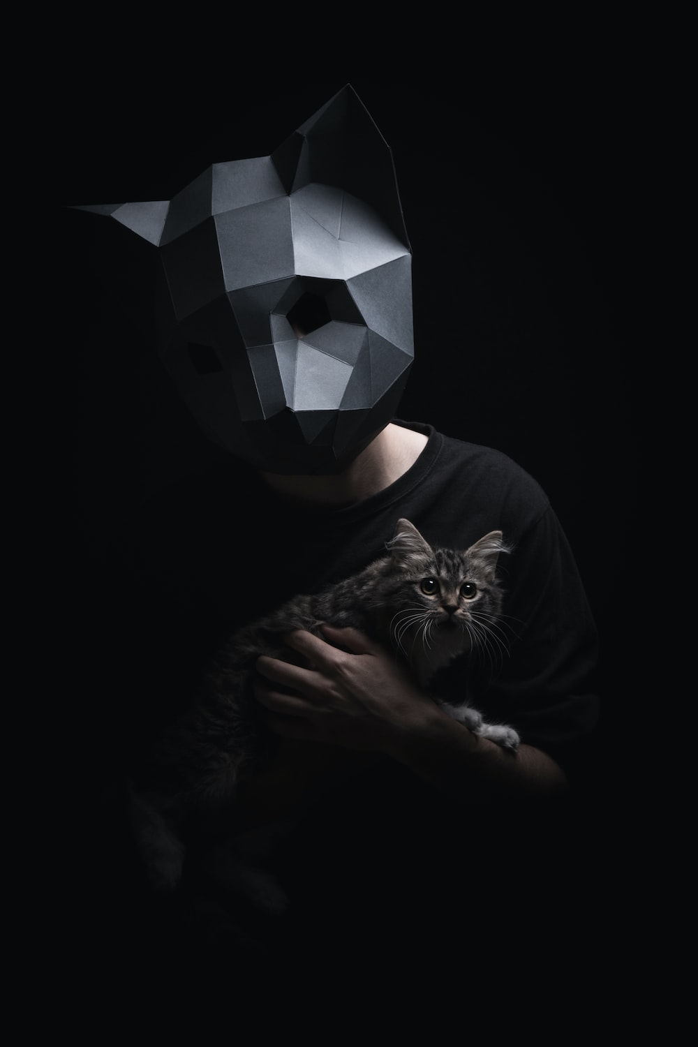 man with mask holding cat