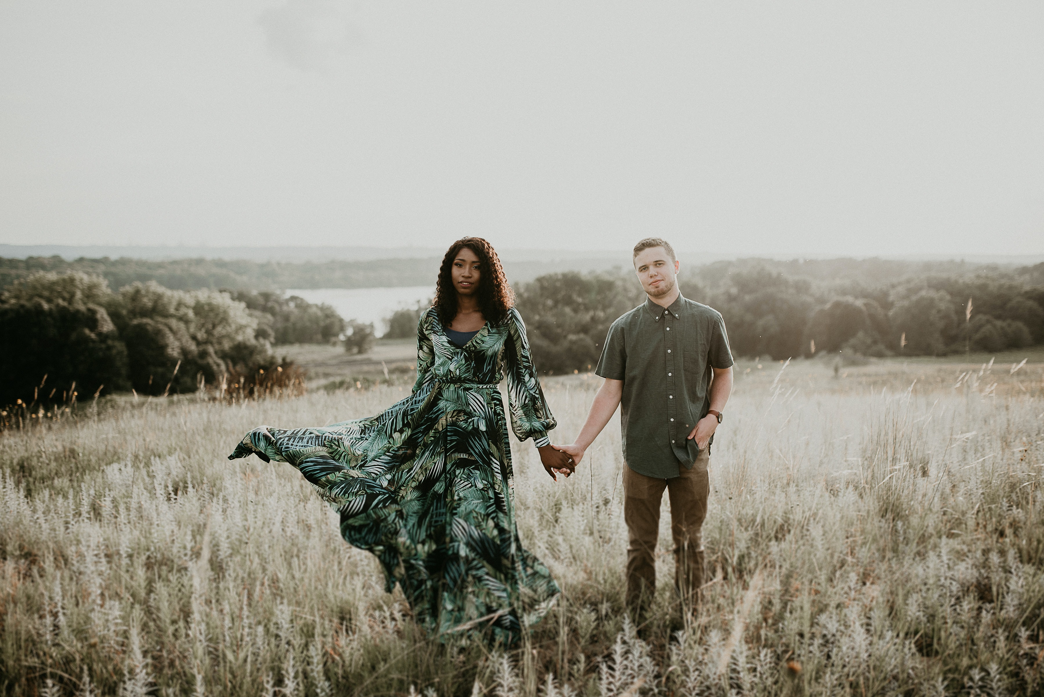 woman in green dress holds mans hand