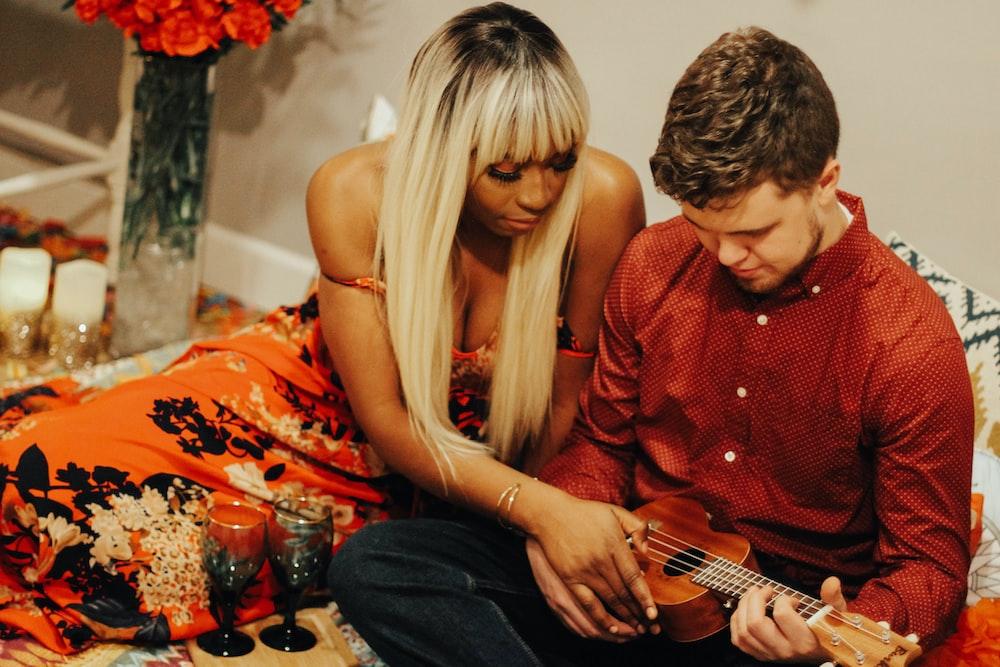 man playing guitar beside woman