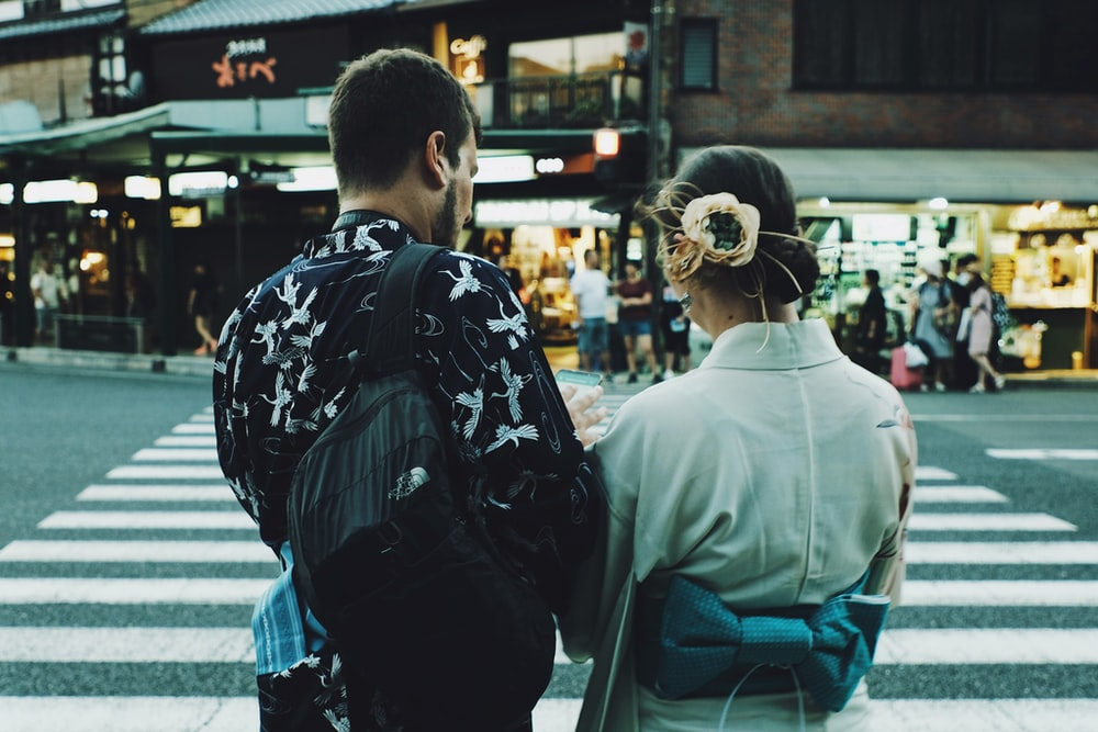man and woman standing front of pedestrian lane