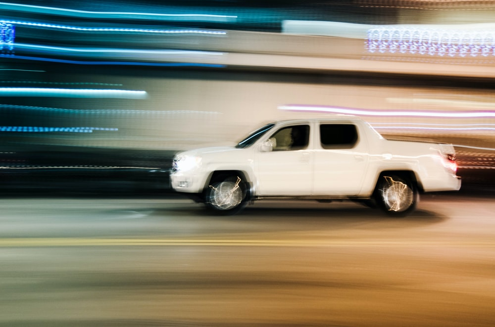 timelapse photography of moving white crew-cab pickup truck
