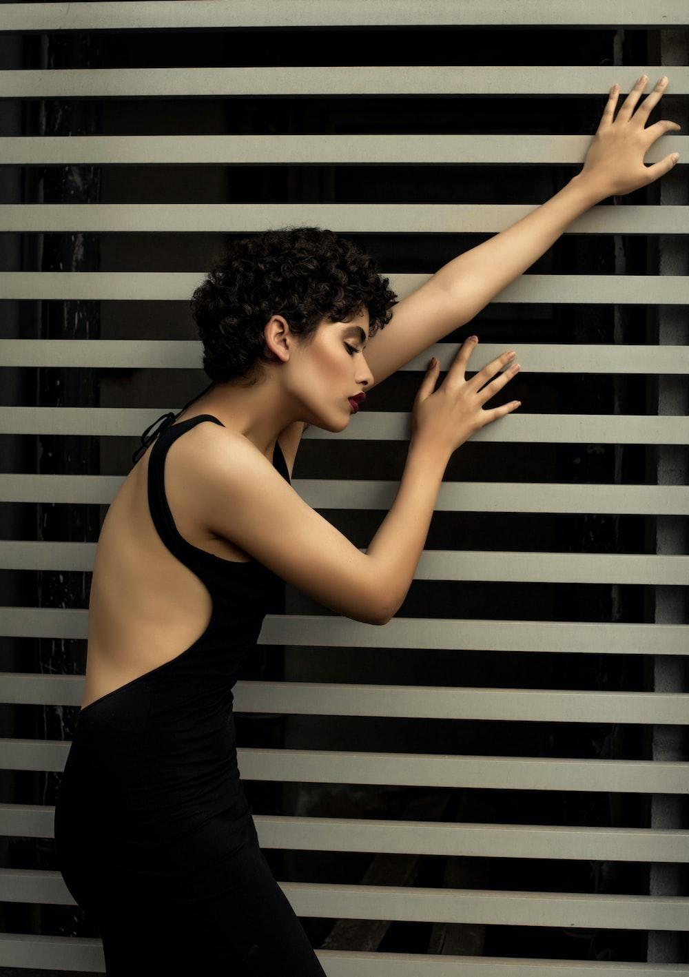 woman in black sleeveless dress learning on window