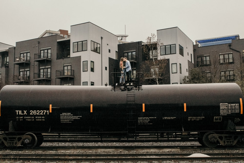 man and woman kissing on train near buildings