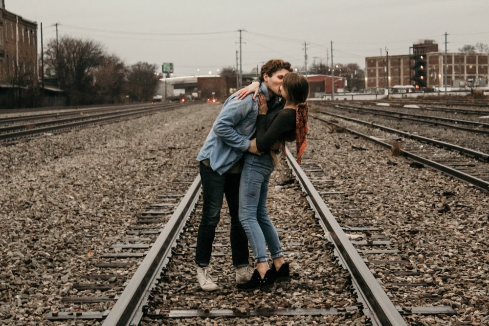 couple kissing in the middle of railroad