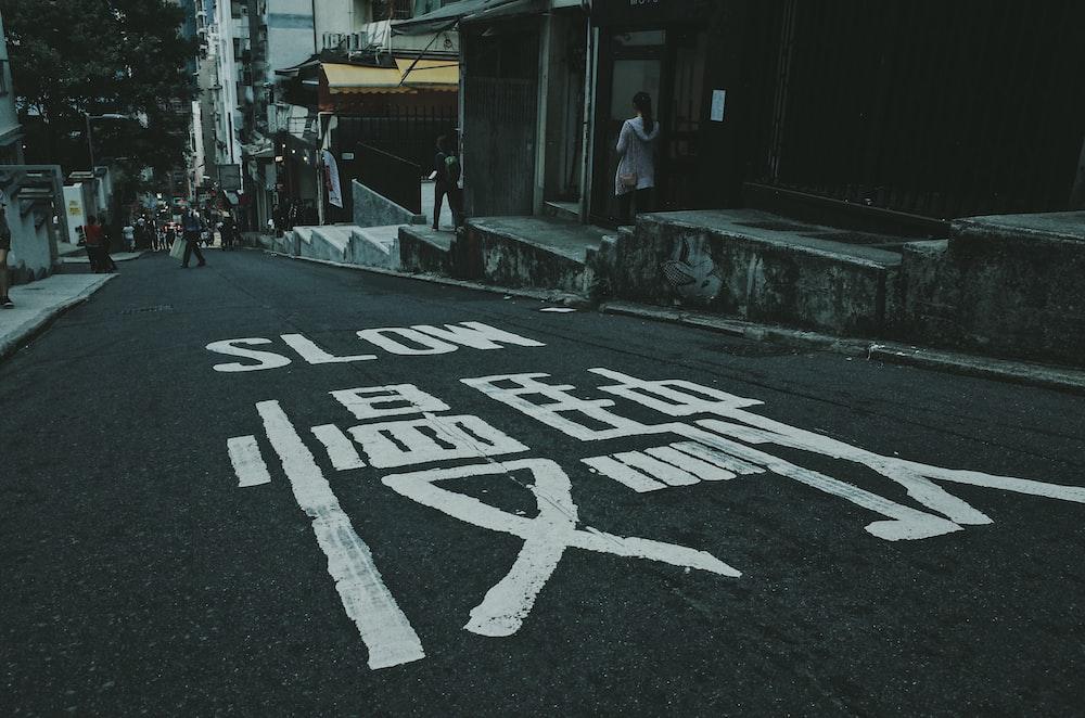 black asphalt road with slow text written