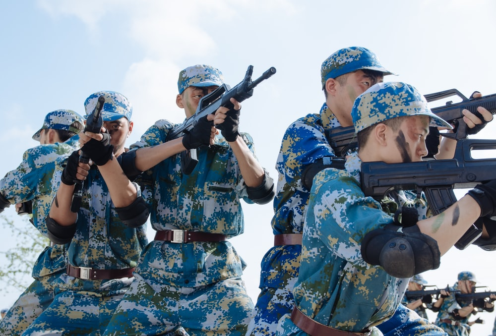 five men pointing rifles during day