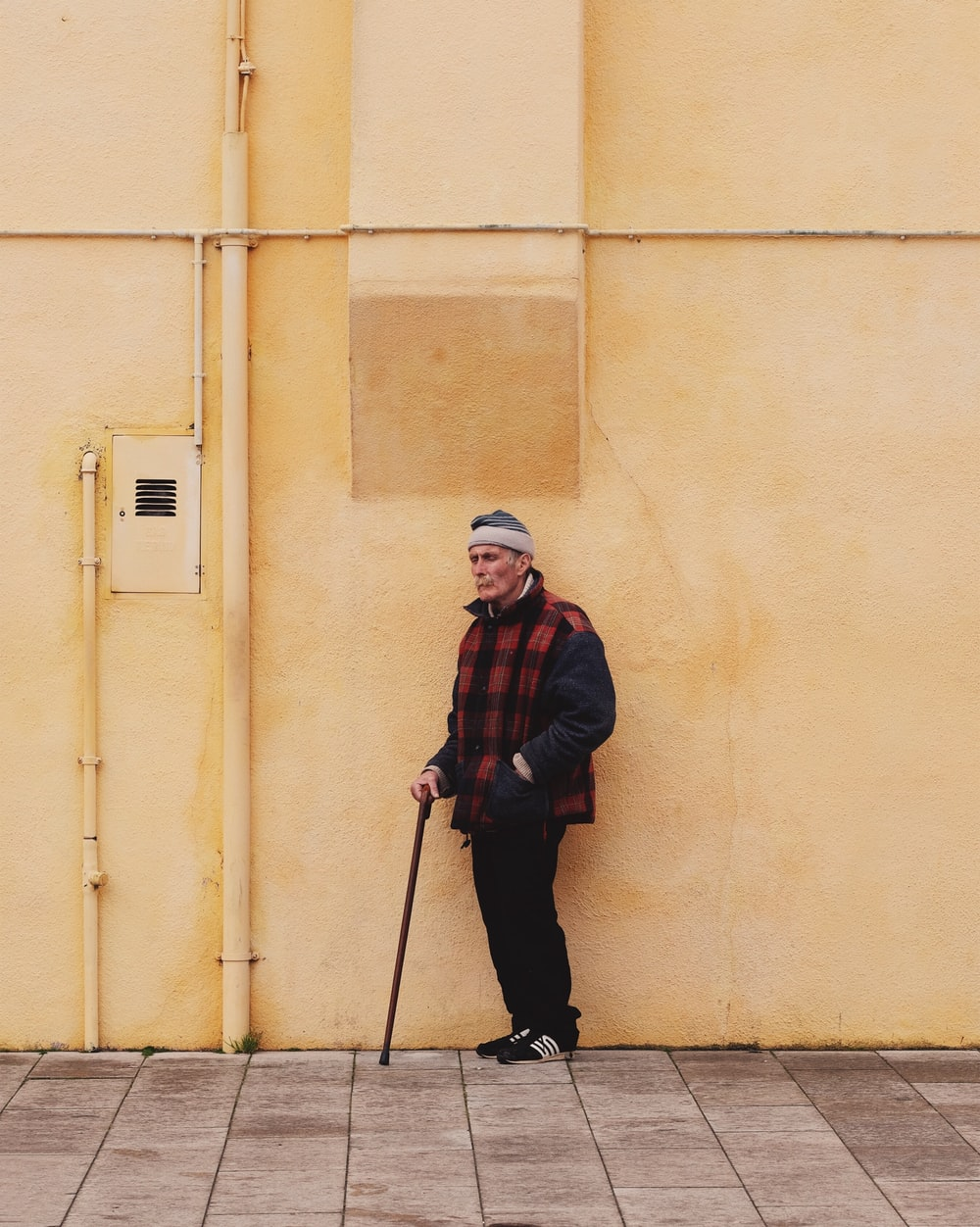 man standing yellow wall