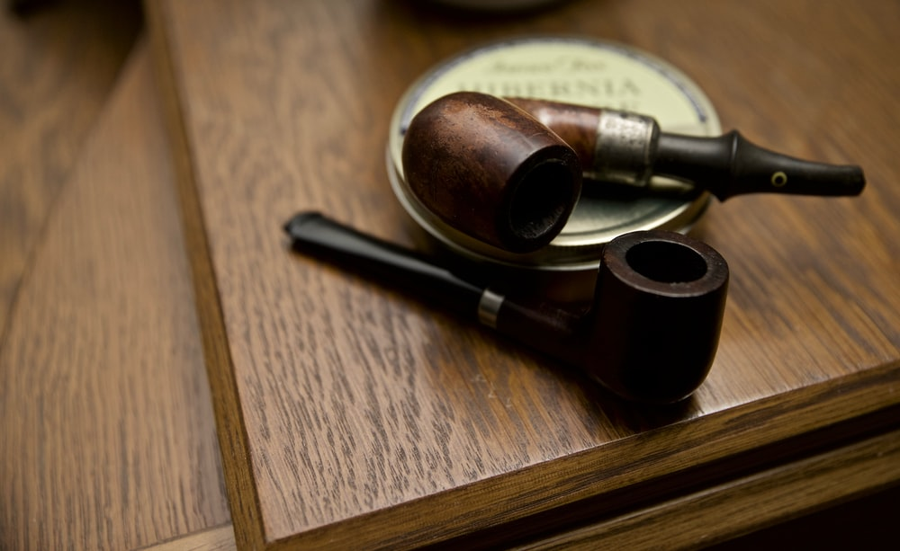 two black and brown wooden smoking pipes on table