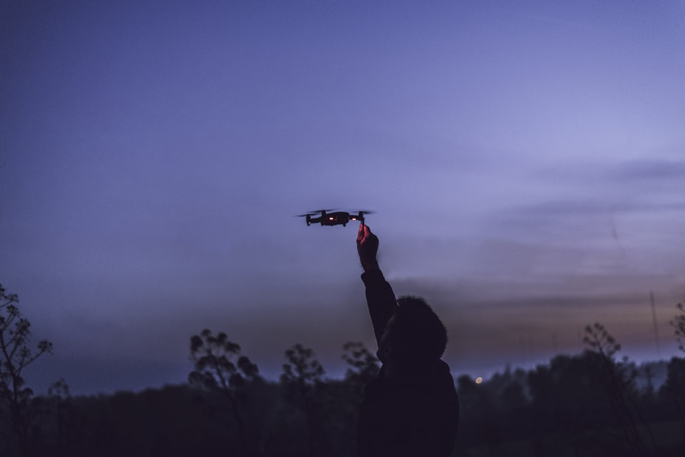 person using black quadcopter drone during nighttime