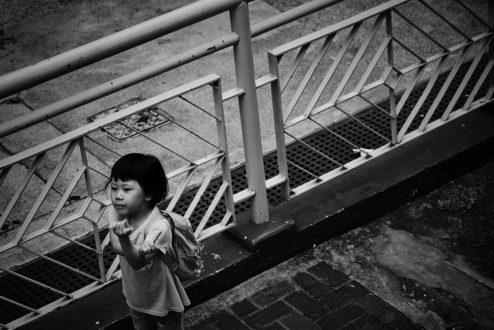 grayscale photography of toddler standing beside rail