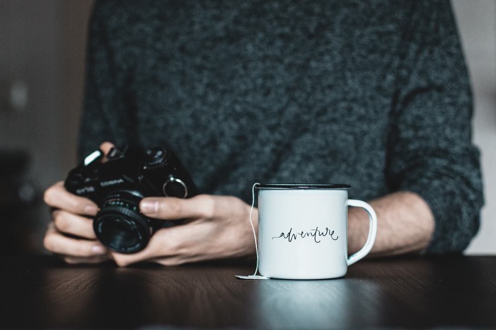 person holding camera near white ceramic mug on table