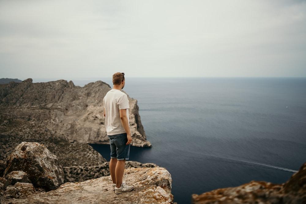 man standing on mountain range near body of water