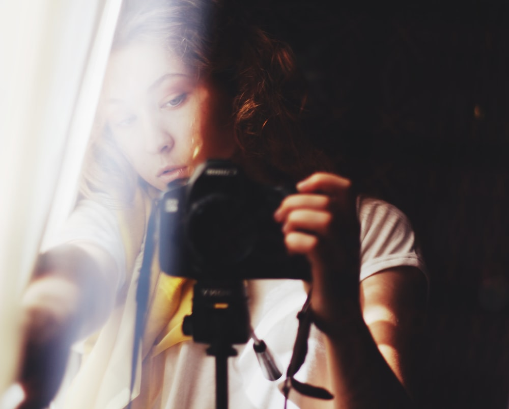 woman holding DSLR camera beside white curtain