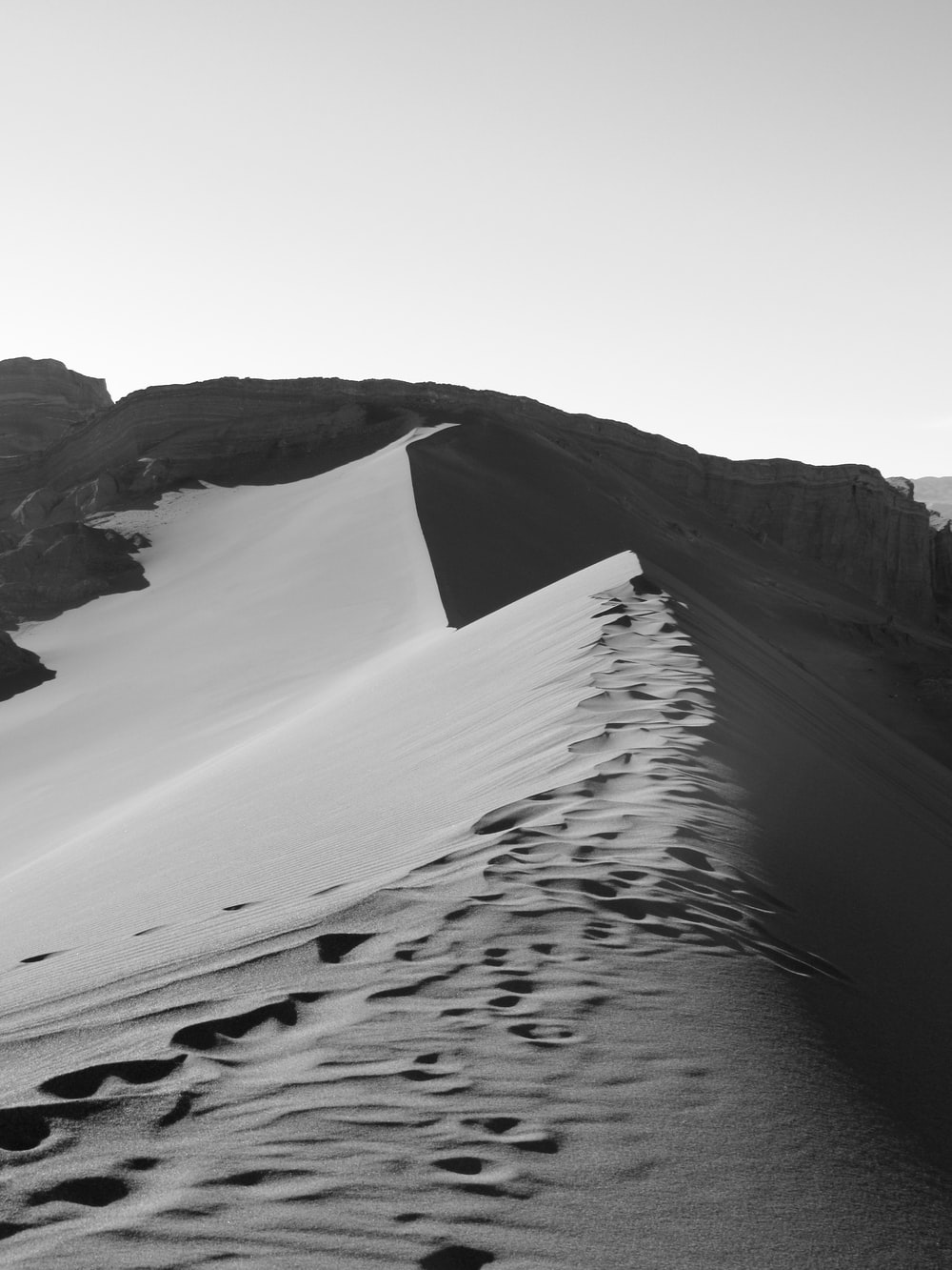 grayscale photography of footprints on desert mountain