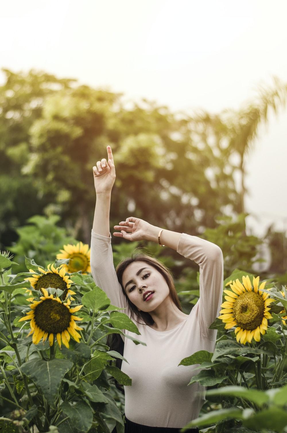 woman raising her hand surround by sunflowers during daytime