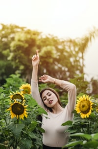 woman raising her hand surround by sunflowers during daytime
