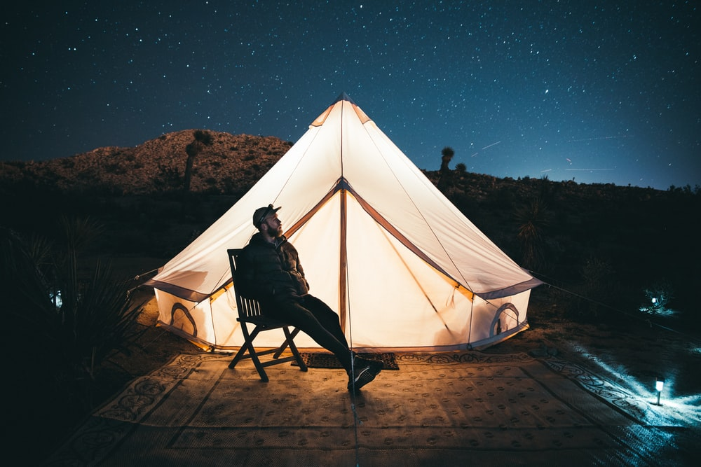 man sitting by tent with light