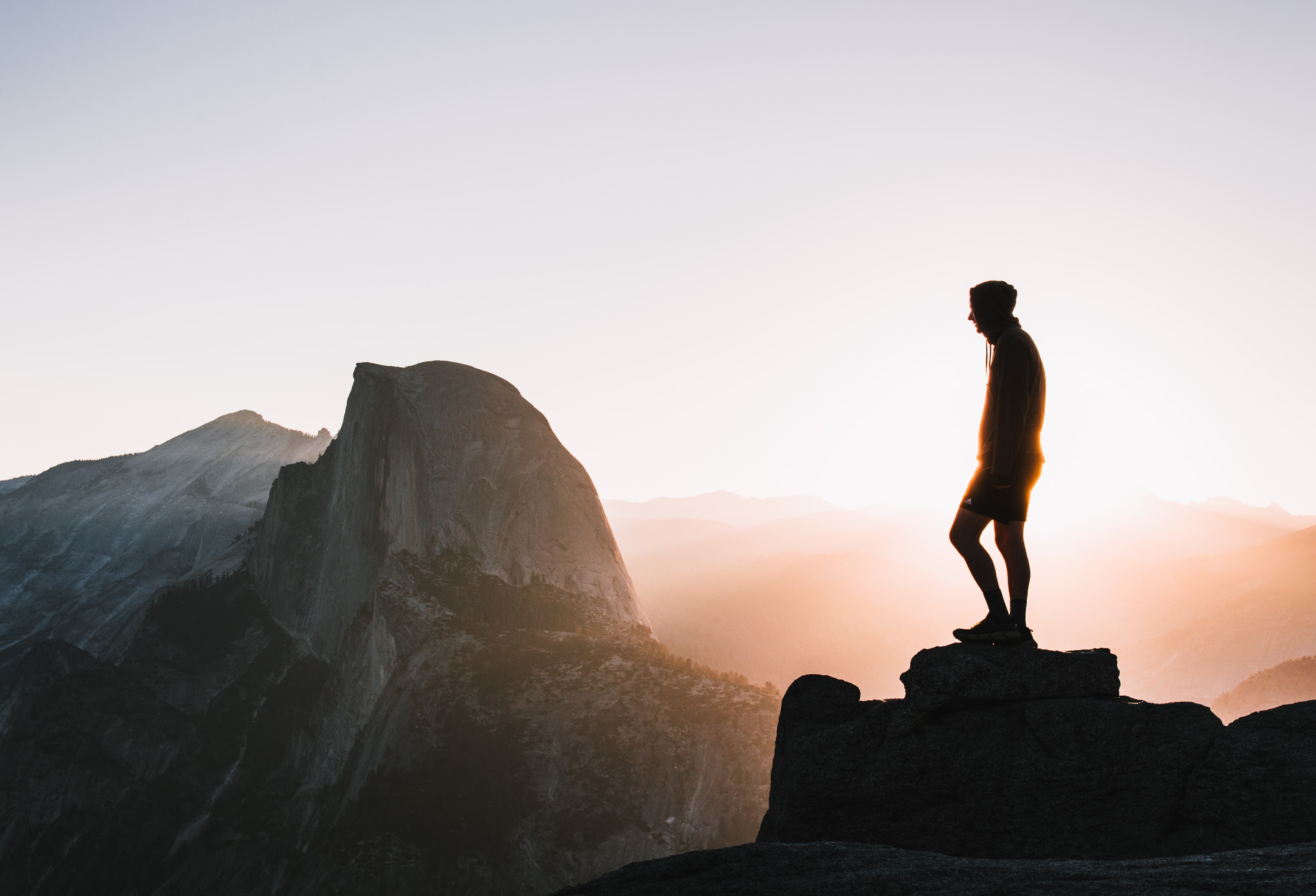 silhouette photo of man standing on hill