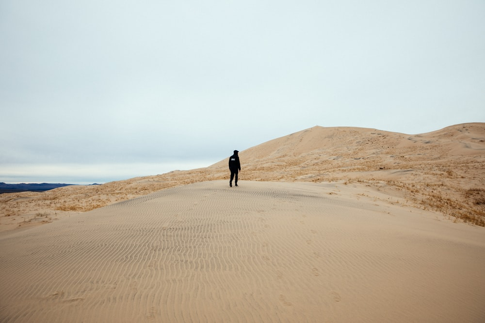 person walking in sand field during daytime