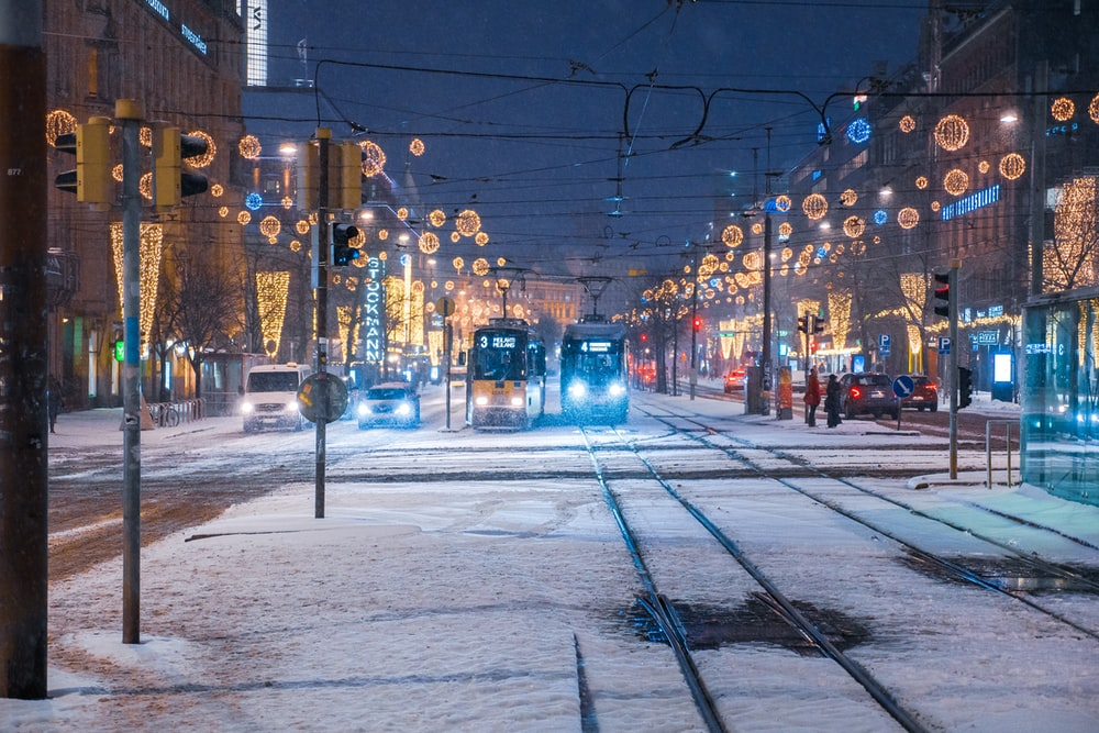 two trams with lights on