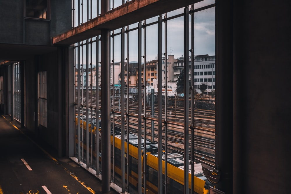 yellow train passing by buildings during daytime
