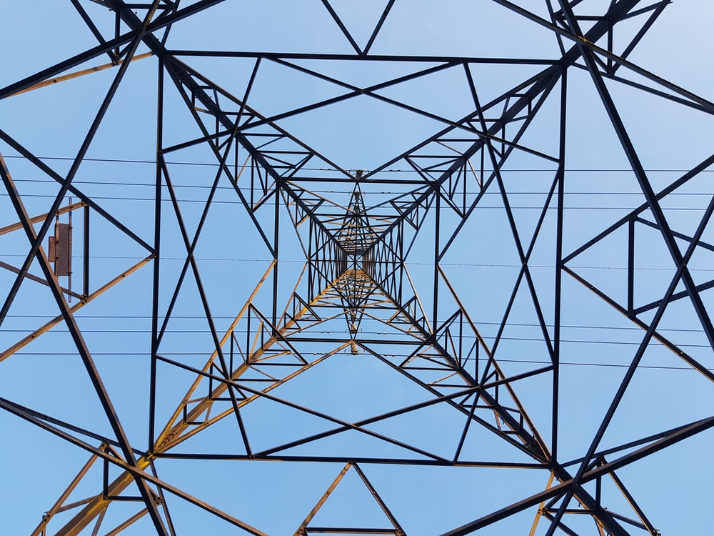 low angle photography of brown metal electric tower