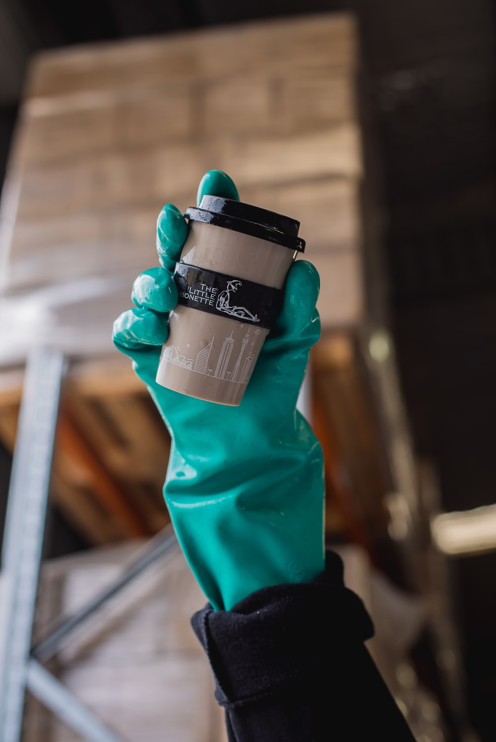 person holding black and gray disposable cup