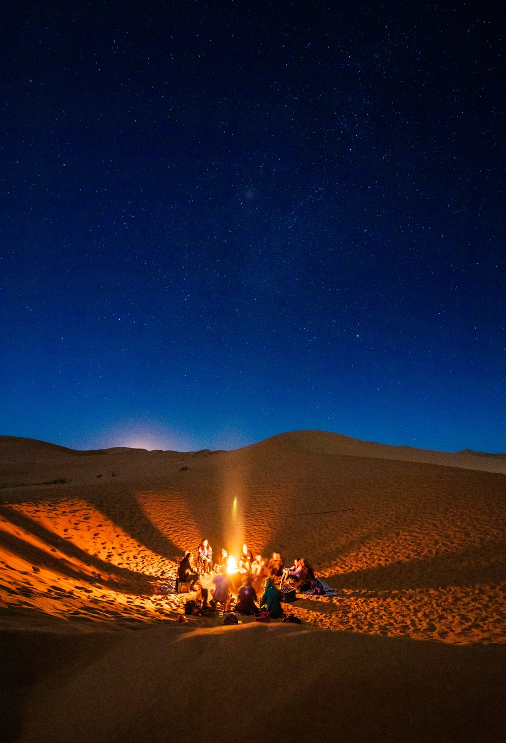 people sitting near bonfire during night time